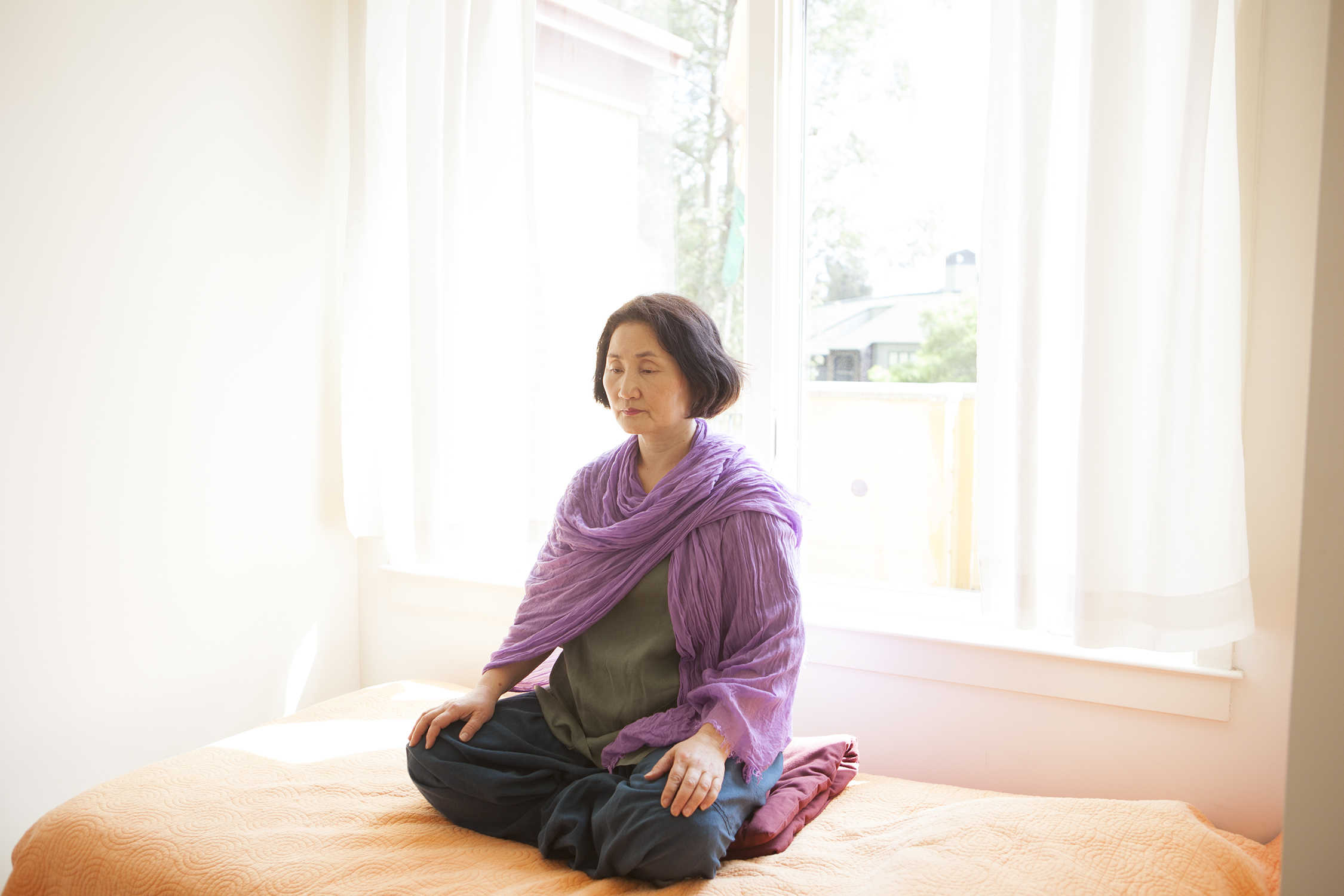 Image of a student meditating on a bed
